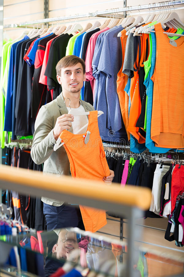 Young man choosing a t-shirt in the store royalty free stock photography