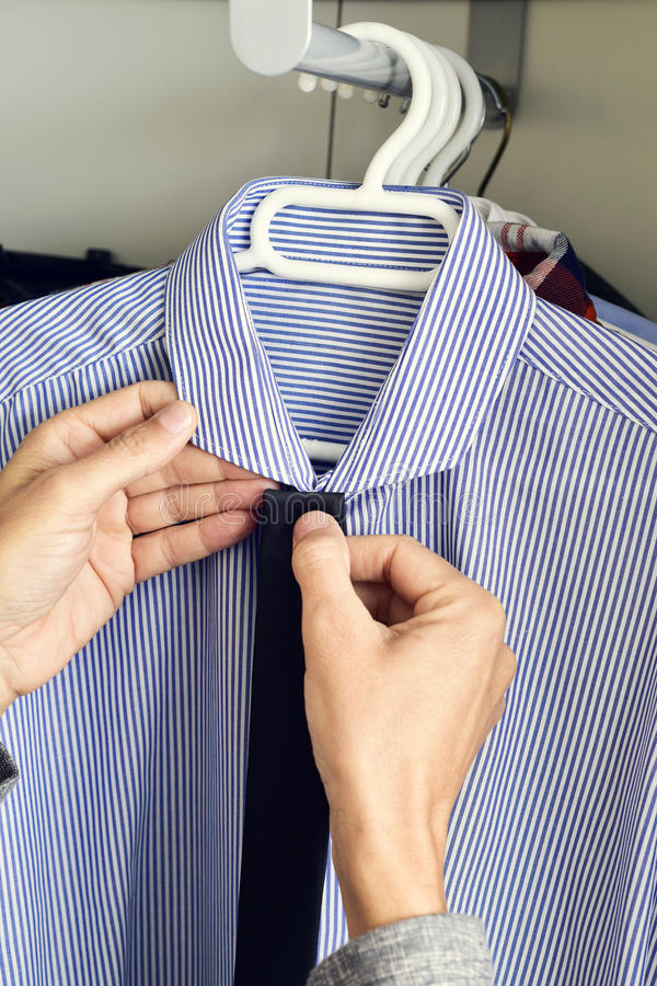 Young man choosing a tie and a shirt from the closet stock images