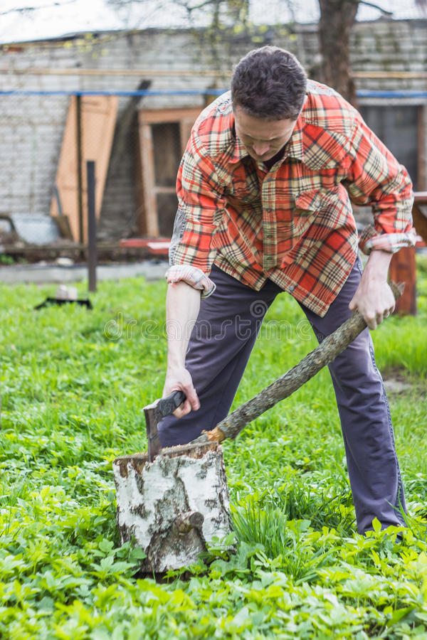 Young man chopping wood stock photography