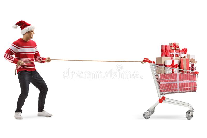 Young man with a christmas hat pulling a shopping cart full of presents with a rope royalty free stock photos