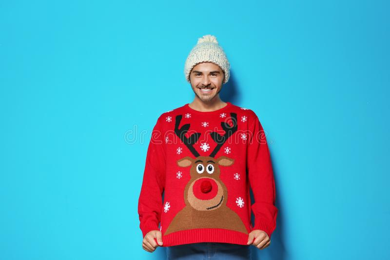 Young man in Christmas sweater and knitted hat. On color background royalty free stock photo