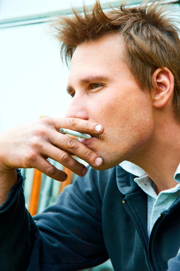 Young man with cigarette in mouth stock images