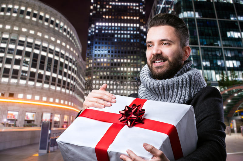 Young man in the city. Young handsome man with Christmas present in the city stock photos