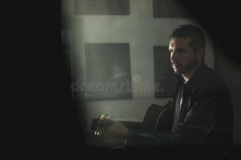 Young man with a classical guitar indoors. Concept Musician guitarist. Young man with a classical guitar indoors. Dramatic portrait of a guitarist royalty free stock photo