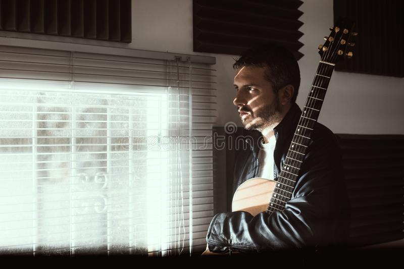 Young man with a classical guitar indoors. Concept Musician guitarist. Young man with a classical guitar indoors. Dramatic portrait of a guitarist stock image
