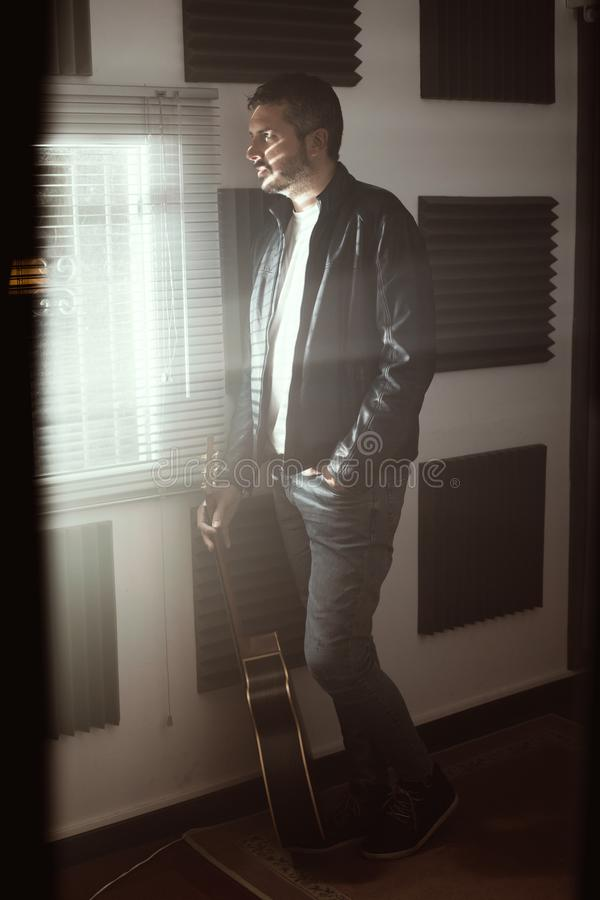 Young man with a classical guitar indoors. Concept Musician guitarist. Young man with a classical guitar indoors. Dramatic portrait of a guitarist stock images