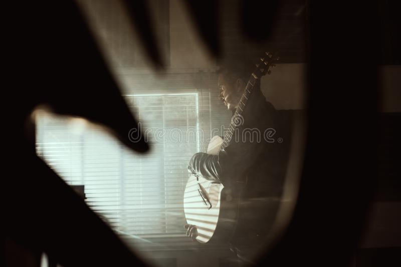 Young man with a classical guitar indoors. Concept Musician guitarist. Young man with a classical guitar indoors. Dramatic portrait of a guitarist stock photography