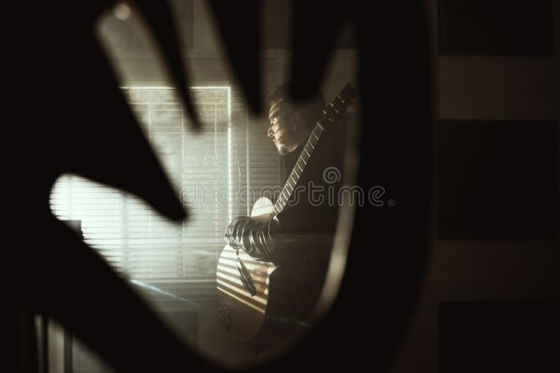 Young man with a classical guitar indoors. Concept Musician guitarist. Young man with a classical guitar indoors. Dramatic portrait of a guitarist stock photo
