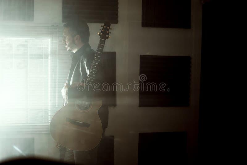 Young man with a classical guitar indoors. Concept Musician guitarist. Young man with a classical guitar indoors. Dramatic portrait of a guitarist stock photos