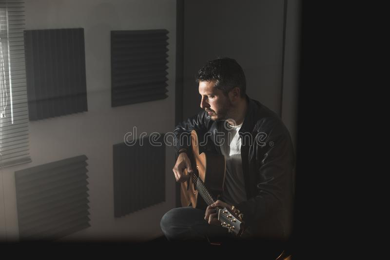 Young man with a classical guitar indoors. Concept Musician guitarist. Young man with a classical guitar indoors. Dramatic portrait of a guitarist royalty free stock image