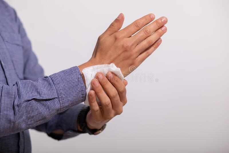 Man cleaning hands with wet wipes royalty free stock photos