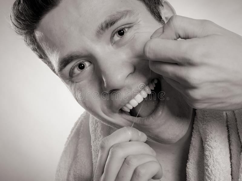 Young man cleaning her white teeth with dental floss. Daily health care. Young man cleaning flossing his white teeth with dental floss, black & white photo royalty free stock photo