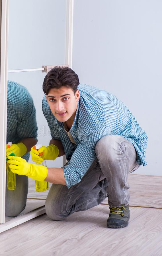 Young man cleaning mirror at home hotel stock image