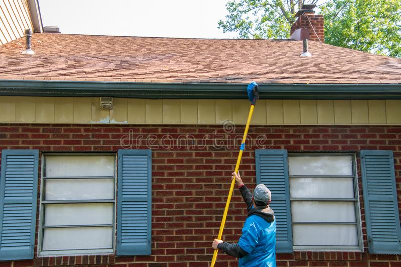 Young man cleaning the soffit of a one story house with a brush on a long pole. The house has blue shutters royalty free stock photography