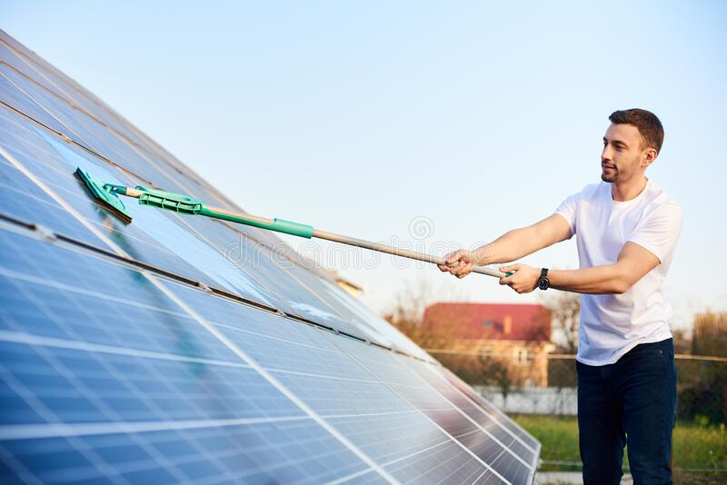 Young man cleaning solar panel stock photo