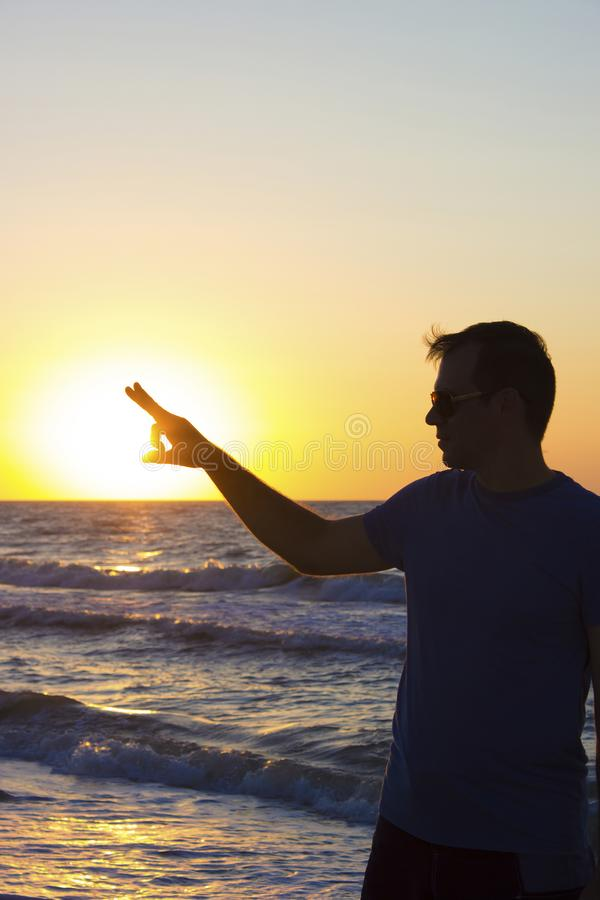 Young man clicks sunrise background blue sky and sea, beach stock images