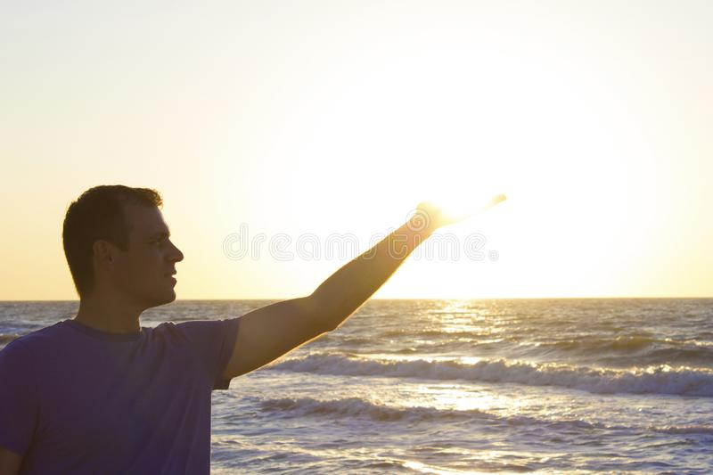 Young man clicks sunrise background blue sky and sea, beach stock photography