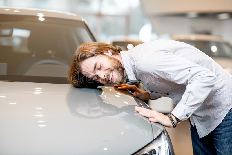 Man hugging new car in the showroom. Young man client touching with face car hood of a new luxury car in the showroom royalty free stock photography