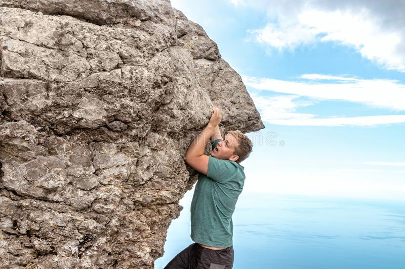 Young man hanging on edge, climbs up the rock stock photo