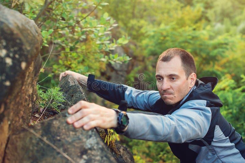 Young man climbing the mountain ridge. Rock climbing, mountain climbing, hiking. Lifestyle, love to mountains. Hiker man on a rock stock images