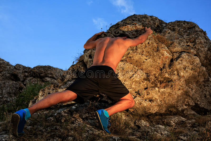 Young man climbing the mountain ridge royalty free stock image