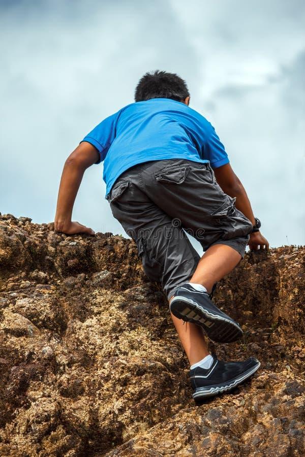 Young Man Climbing a Mountain stock photos