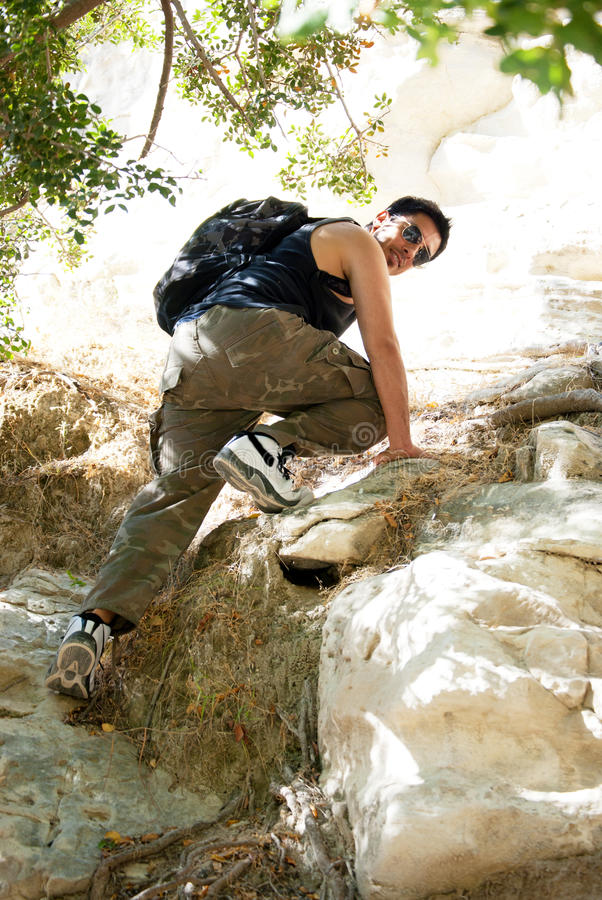 Young man climbing stock image