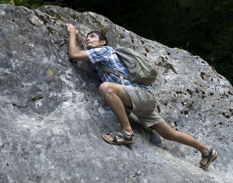 Young man climbing rock stock photography