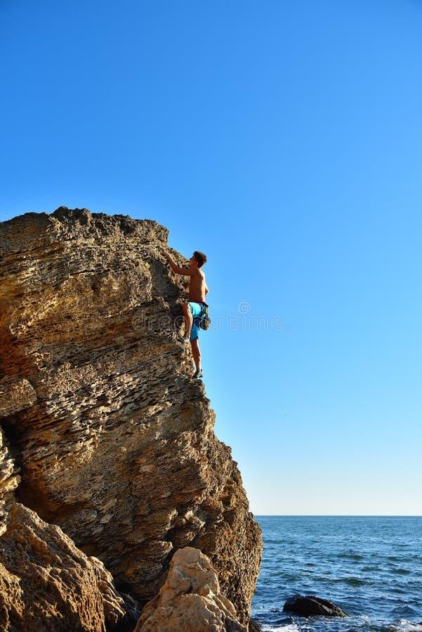 Young man climbing up on yellow mountain stock photo