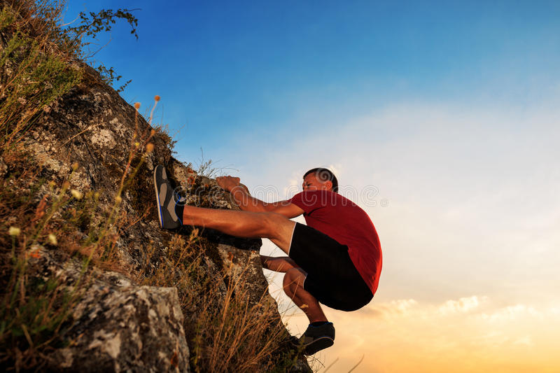 Young man climbing on a wall stock images