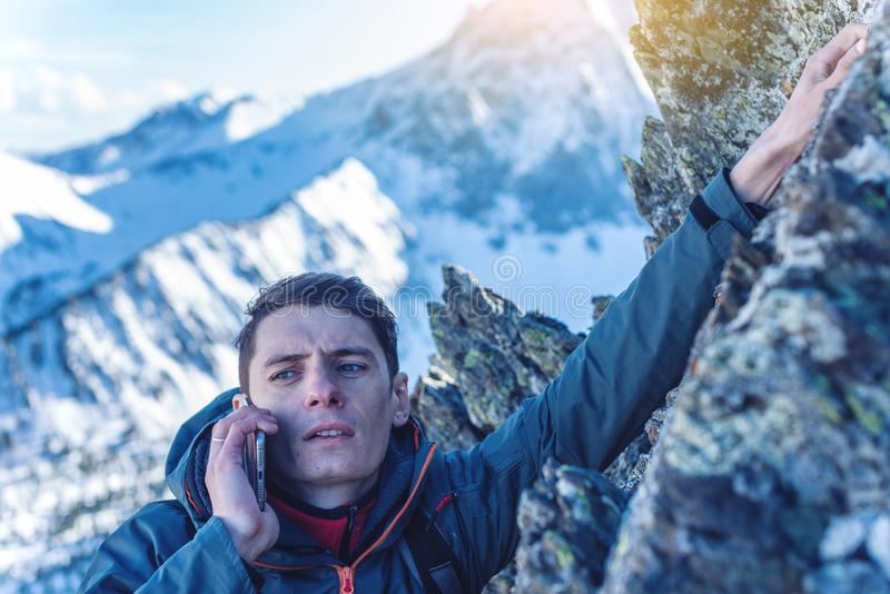 A young man climbs the mountain to the top and talking holding the phone. Concept of persistence and goal achievement royalty free stock image