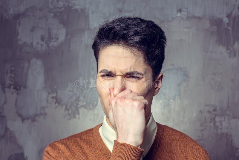 Young man closing nose stock photos