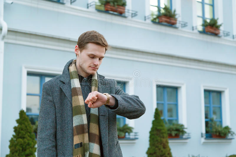 Young man in coat is looking at his watch while standing outdoors in the city. Time appointment Concept. stock photography
