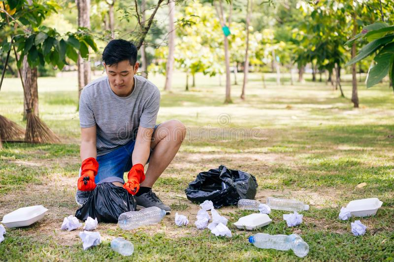 Young man collecting trash in garbage bag in the park stock photos