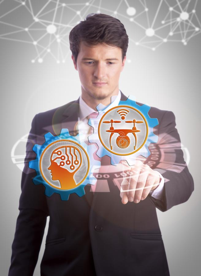 Young Man Combing UAV And AI Into Smart Drone. Intent young IT manager operating drone and artificial intelligence app via touch screen monitor. Technology royalty free stock image