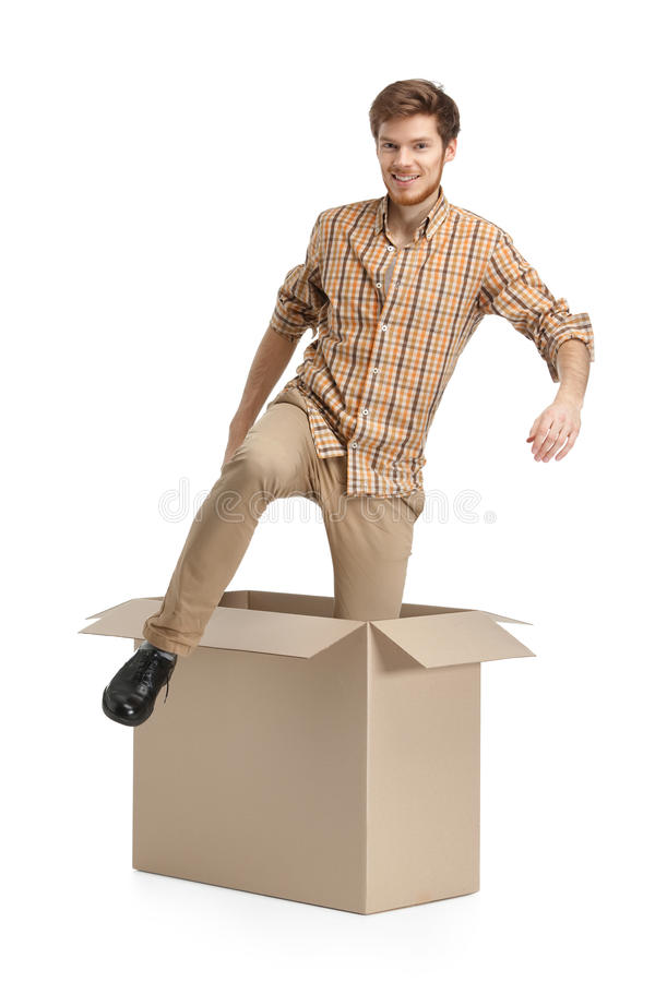 Young Man Comes Out Of The Cardboard Box Royalty Free Stock Photos