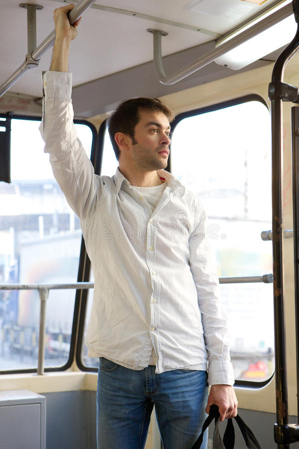 Young man commuting by tram. Portrait of a young man commuting by tram stock photo