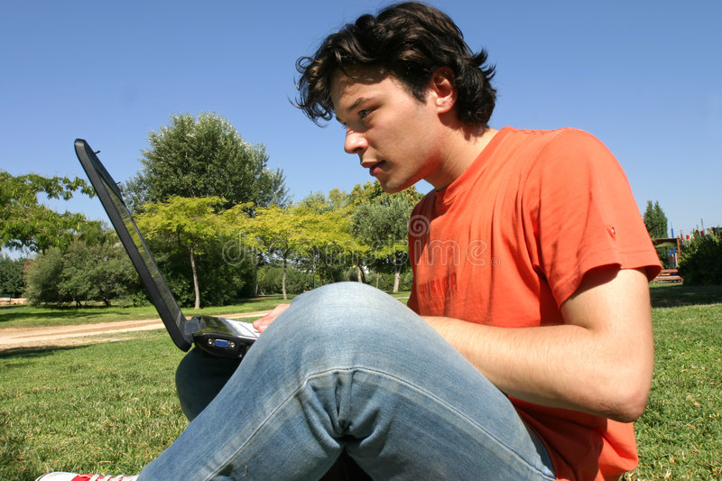 Young man with computer. Young man working with a computer outside stock photo