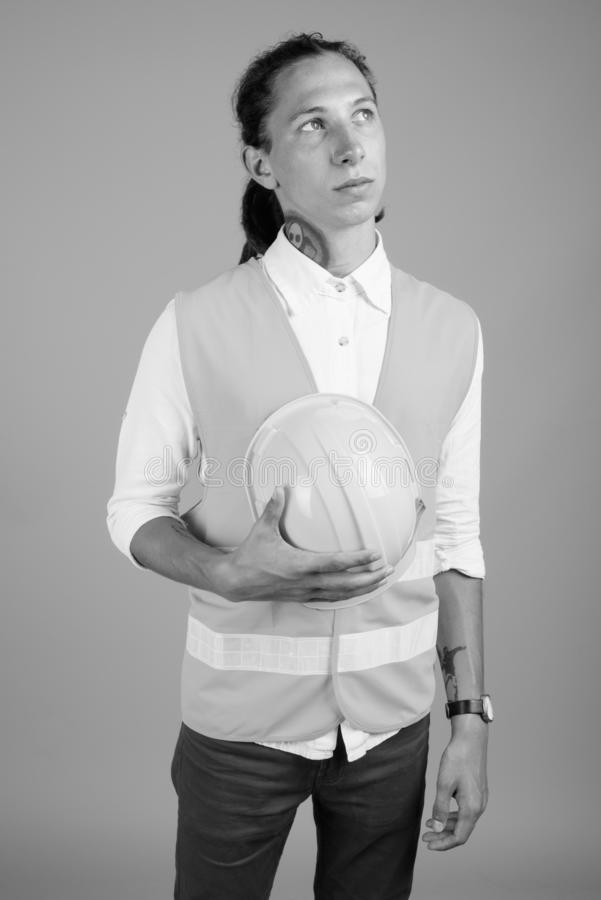 Young man construction worker in black and white. Studio shot of young man construction worker with dreadlocks against gray background in black and white royalty free stock image