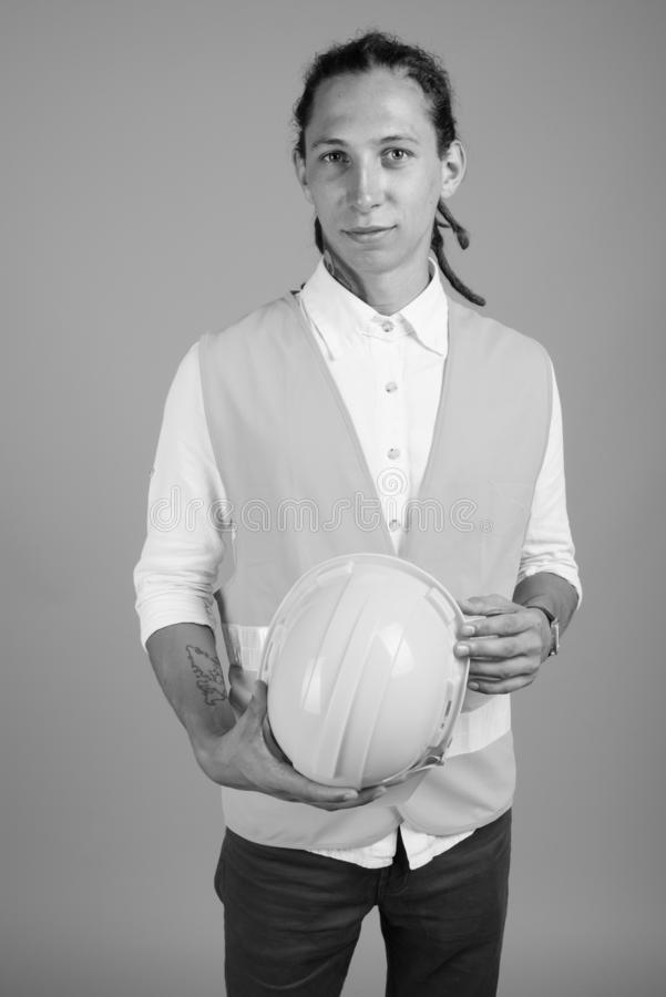 Young man construction worker in black and white. Studio shot of young man construction worker with dreadlocks against gray background in black and white royalty free stock photos