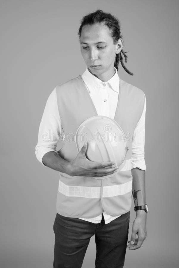 Young man construction worker in black and white. Studio shot of young man construction worker with dreadlocks against gray background in black and white royalty free stock images