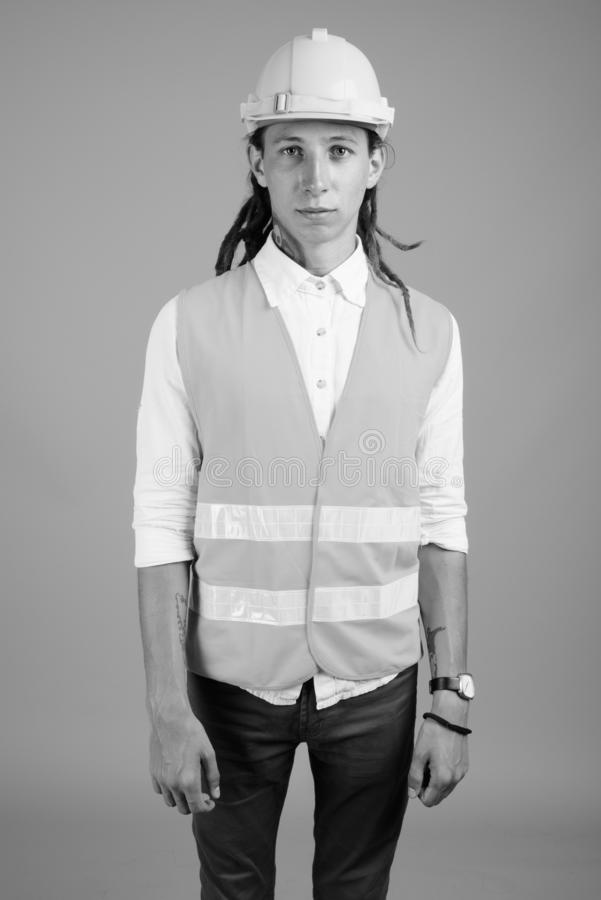 Young man construction worker in black and white. Studio shot of young man construction worker with dreadlocks against gray background in black and white royalty free stock photo