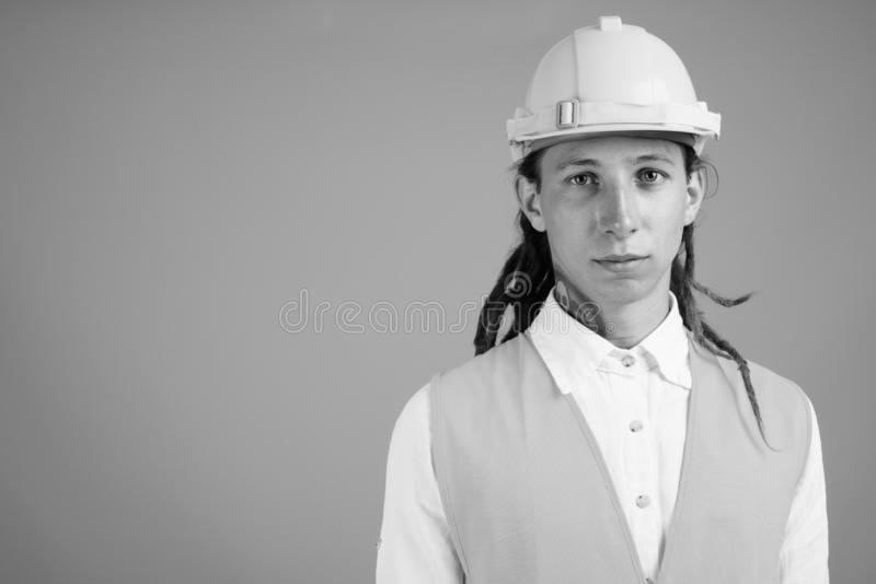 Young man construction worker in black and white. Studio shot of young man construction worker with dreadlocks against gray background in black and white royalty free stock photography