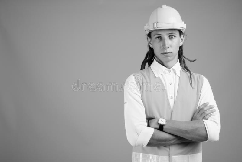 Young man construction worker in black and white. Studio shot of young man construction worker with dreadlocks against gray background in black and white stock photography
