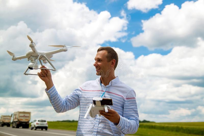 Young man controlling drone in field. Drone operator holding a transmitter. royalty free stock photography