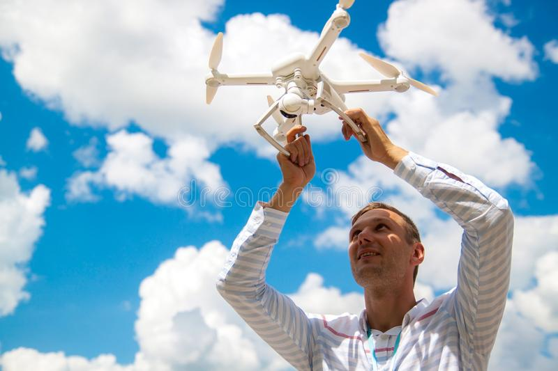 Young man controlling drone in field. Drone operator holding a transmitter. stock image