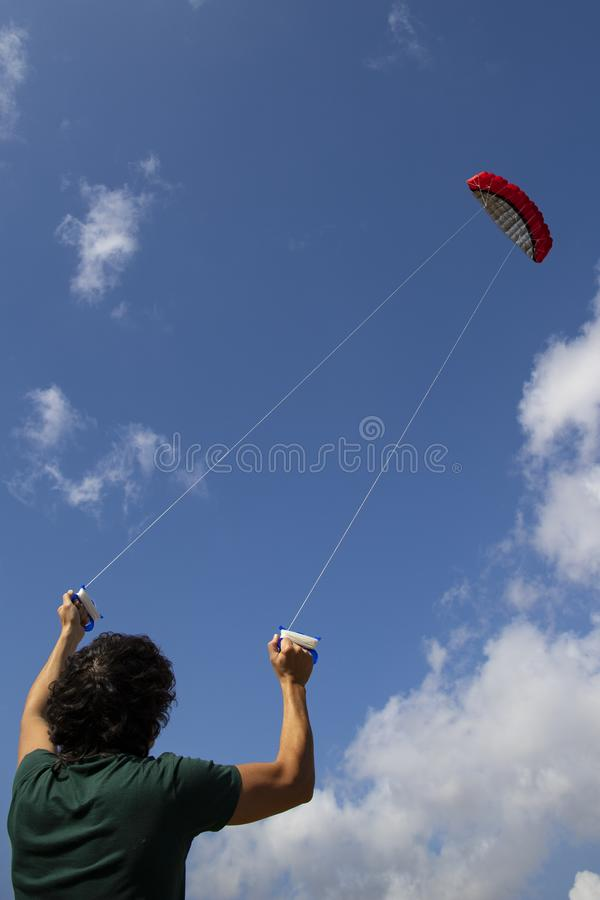 Young man controlling a red kite in the blue sky. Young man, back view,  controlling a red kite with blue sky in the background. Vertical shot royalty free stock photography