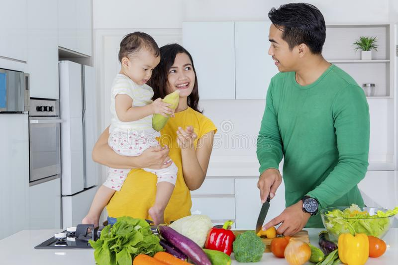 Young man cooking with his wife and daughter stock photography