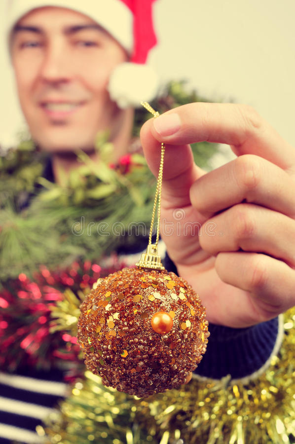 Young man covered with christmas ornaments royalty free stock image