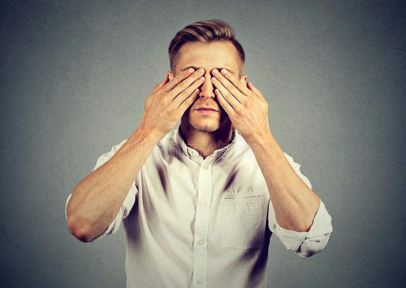 Young man covering eyes with both hands. Man covering eyes with hands stock photos